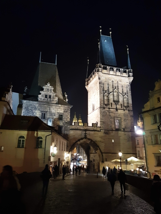 bustling shadows amid silhouetted statues of nearby Charles Bridge
